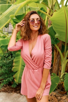Sexy europäische frau mit den lockigen haaren im rosa kleid, das über palmen steht. sommermode.