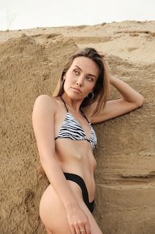 Sexy fit verführerische frau im bikini am sandstrand, entspannend, sonnenbaden. junge schlanke, attraktive asiatische frau im badeanzug, die allein in der natur chillt. sommerurlaub, entspannung, ruhe, sexualität