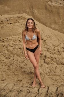 Sexy fit verführerische frau im bikini beim sonnenbaden allein am sandstrand