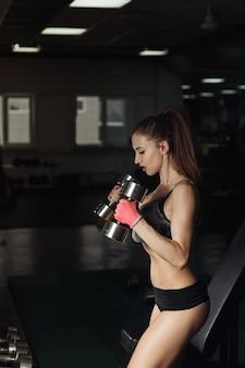 Sexy fitness-frau in sportkleidung mit perfektem fitness-körper im fitnessstudio, die übungen mit hantel durchführt