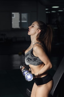 Sexy fitness-frau in sportkleidung mit perfektem fitness-körper in der turnhalle, die übungen mit hantel durchführt.