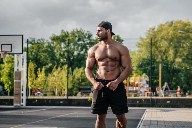 Sexy fitness-sportler, der oben ohne auf einem sportplatz aufwirft. fitness, bodybuilding, gesunder lebensstil