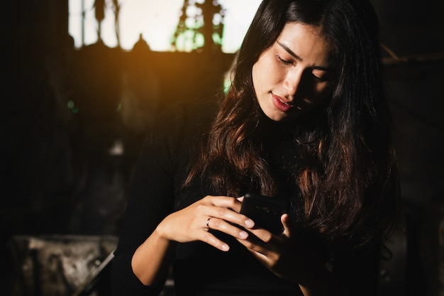 Sexy frau asiens, die smartphone in der freizeit mit glücklichem verwendet.