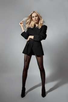 Sexy frau der schönheitsmode in der jacke und in den strumpfhosen, blondes mädchen mit den langen beinen. perfekte figur des models