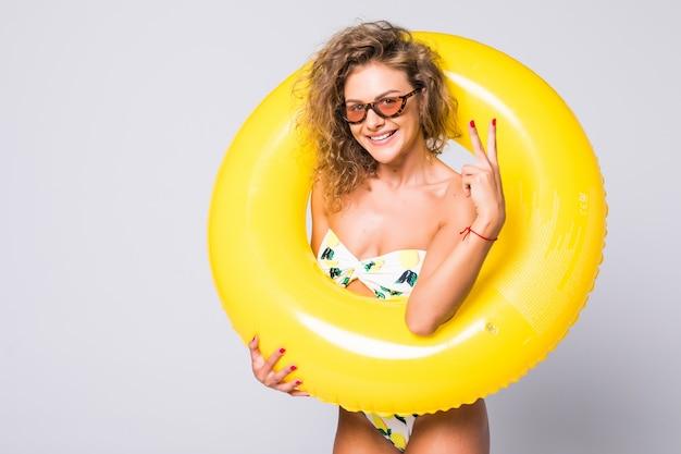 Sexy frau des ganzen körpers im bikini mit gelbem aufblasbarem ring lokalisiert über weißer wand