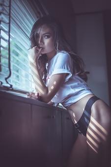Sexy frau, die am fenster steht