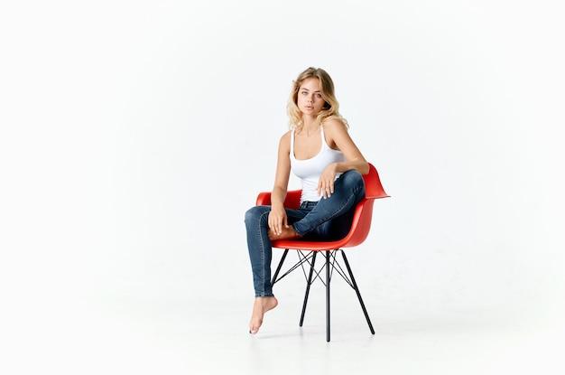 Sexy frau, die auf rotem stuhl drinnen im vollen wachstumsmodell sitzt