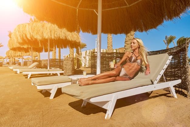 Sexy frau, die den bikini trägt, der auf der liege unter dem strohdachregenschirm am strand sitzt und glas mit cocktail oder getränk hält