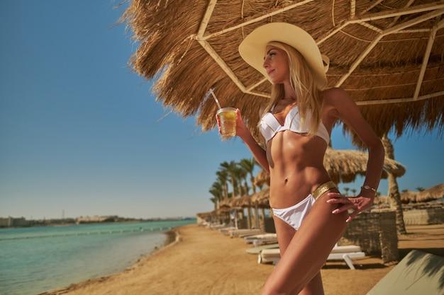 Sexy frau, die den bikini trägt, der unter dem strohdachregenschirm am strand steht und glas mit cocktail oder getränk hält.