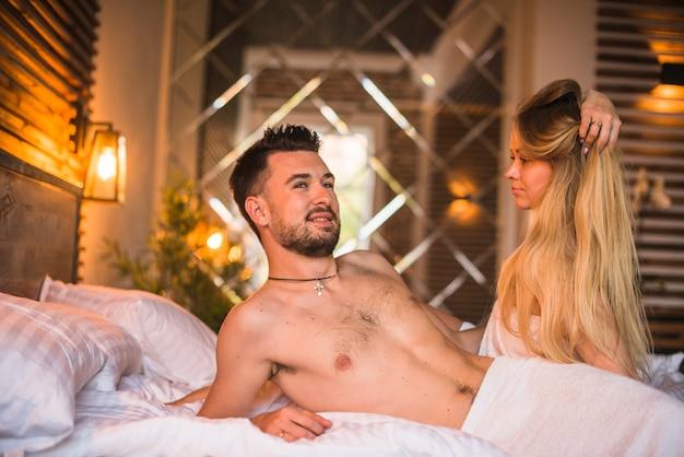 Sexy frau, die den hemdlosen mann liegt auf bett betrachtet
