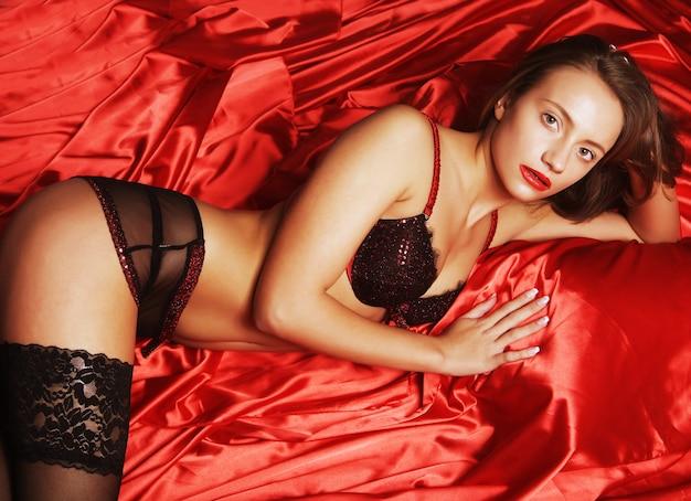 Sexy frau, die dessous trägt, die auf bett liegen