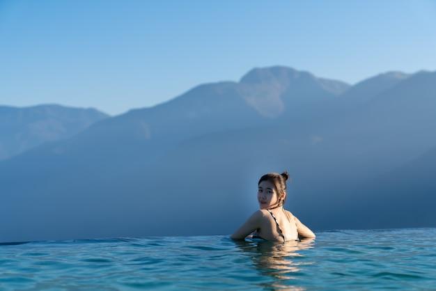 Sexy frau, die im infinity-schwimmbad mit atemberaubendem bergblick am luxuriösen resort- / urlaubskonzept entspannt