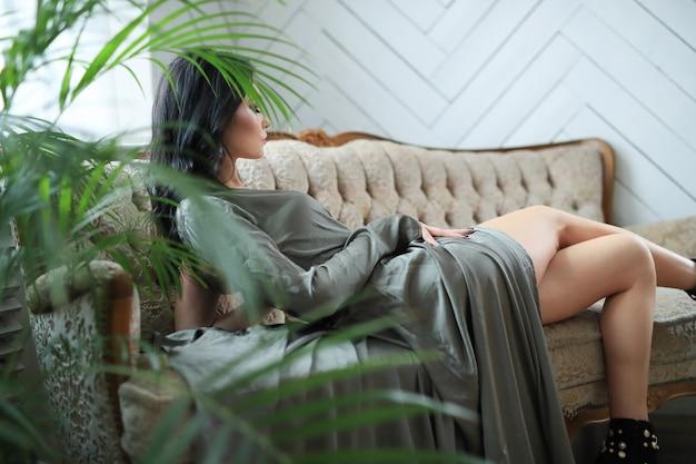 Sexy frau, die im sofa mit einem sexy kleid liegt