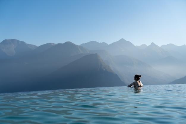 Sexy frau, die im unendlichen schwimmbad entspannt, das atemberaubenden bergblick am luxuriösen resort- / urlaubskonzept betrachtet