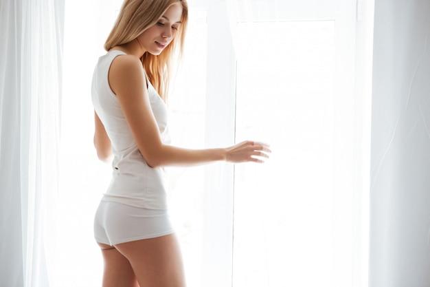 Sexy frau, die nahe am fenster steht