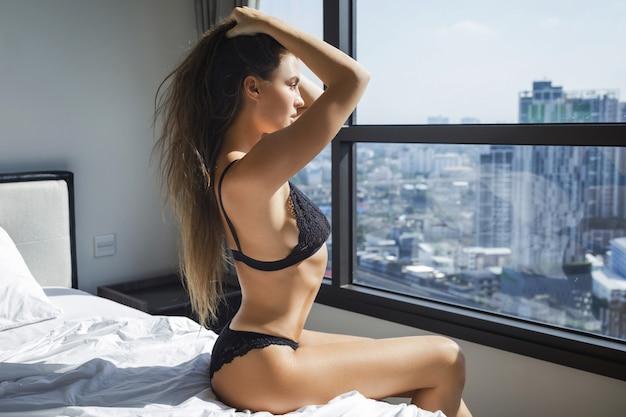Sexy frau, die schwarze dessous trägt, die auf dem bett sitzen