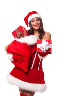 Sexy frau, die weihnachtsgeschenke vom sack des weihnachtsmanns gibt