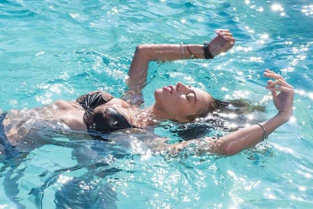 Sexy frau entspannen im schwimmbad, erfrischung und hautpflege