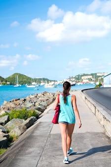 Sexy frau geht am meer entlang in st.thomas, britische jungferninsel. frau in top und shorts an der strandpromenade am sonnigen tag, rückansicht, strandmode. sommerurlaub auf der insel, fernweh.