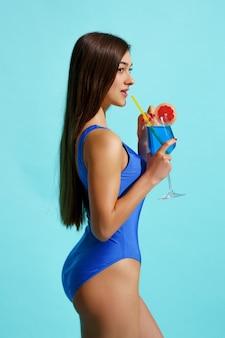 Sexy frau im badeanzug wirft mit cocktail, seitenansicht auf. mädchen in badebekleidung