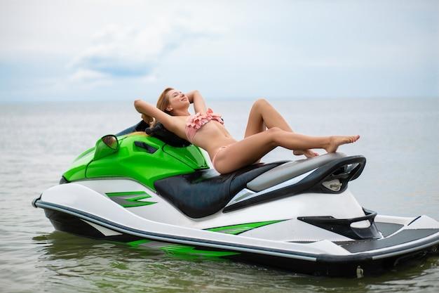 Sexy frau im bikini auf wasserscooter im seesommerstil