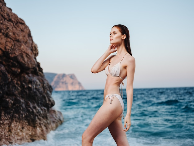 Sexy frau im bikini-badeanzug am strand nahe dem ozean mit weißem schaum. hochwertiges foto