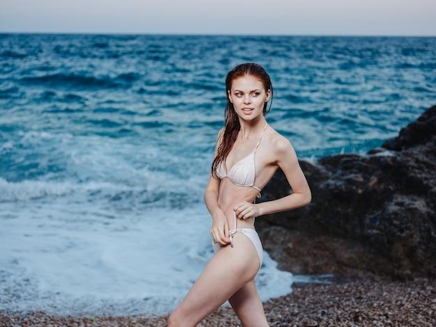 Sexy frau im bikini-badeanzug am strand nahe dem ozean mit weißem schaum