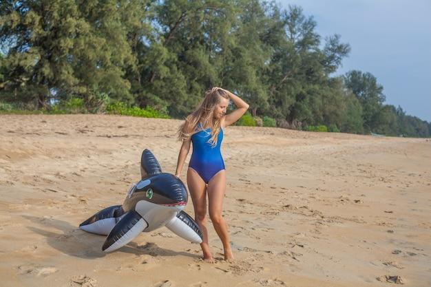 Sexy frau im blauen badeanzug am strand mit aufblasbaren spielzeug
