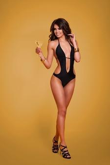 Sexy frau im luxuriösen badeanzug, der martini trinkt