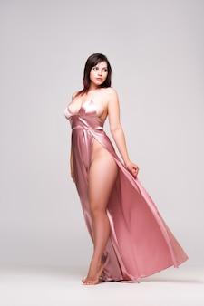 Sexy frau im rosa kleid mit tiefem ausschnitt auf grauer wand, porträt in voller länge