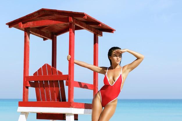 Sexy frau im roten badeanzug neben rettungsschwimmerturm