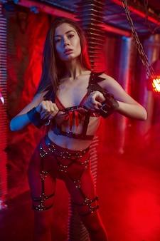 Sexy frau im roten bdsm-anzug hält lederpeitsche, verlassenes fabrikinterieur. junges mädchen in erotischer unterwäsche, sexfetisch, sexuelle fantasie
