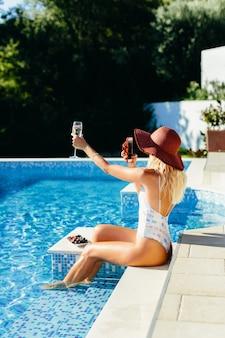 Sexy frau im schwimmbad im freien entspannen. schöne frau trinkt champagner und isst früchte.