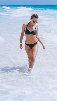 Sexy frau im schwimmenabnutzungsbikini im ozeanwasser