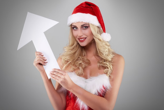 Sexy frau im weihnachtsmannkostüm auf grauer wand Kostenlose Fotos