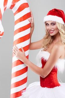 Sexy frau im weihnachtsmannkostüm auf grauer wand