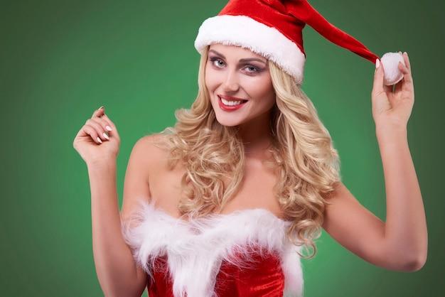 Sexy frau im weihnachtsmannkostüm auf grüner wand