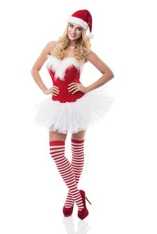 Sexy frau im weihnachtsmannkostüm, das auf weißer wand aufwirft