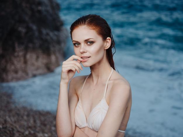 Sexy frau im weißen badeanzug nahe dem meer und schaumstrand rockt die natur. hochwertiges foto