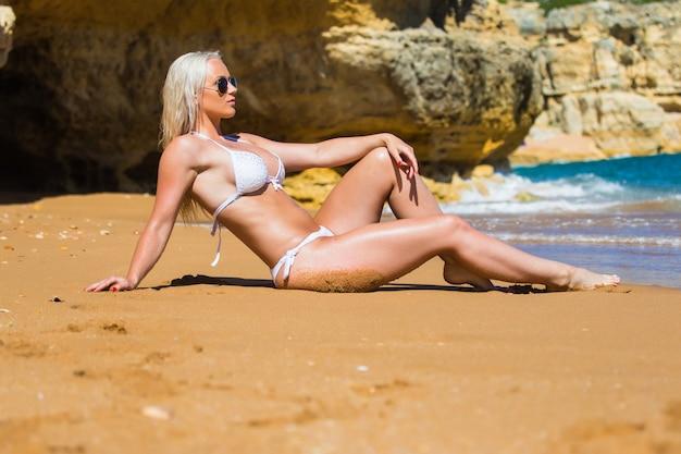 Sexy frau im weißen badeanzug posiert auf dem felsen neben schönem blauem wasser