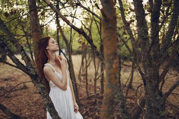Sexy frau im weißen sommerkleid nahe bäumen im garten.