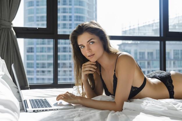 Sexy frau in den schwarzen dessous, die auf dem bett liegen und laptop verwenden