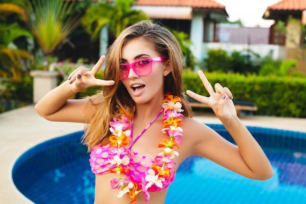 Sexy frau in den sommerferien, die spaß am pool tragen bikini und rosa sonnenbrille, tropische blumen, bunte sommermode-art tragen