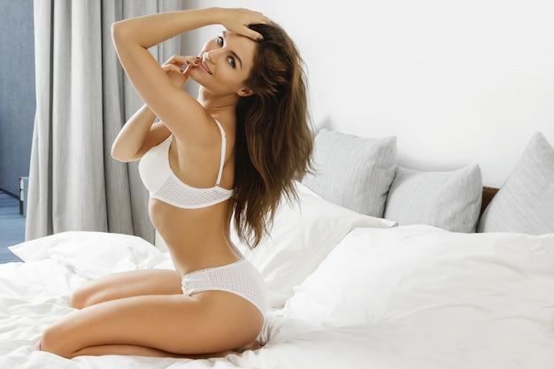 Sexy frau in den weißen dessous, die auf dem bett sitzen