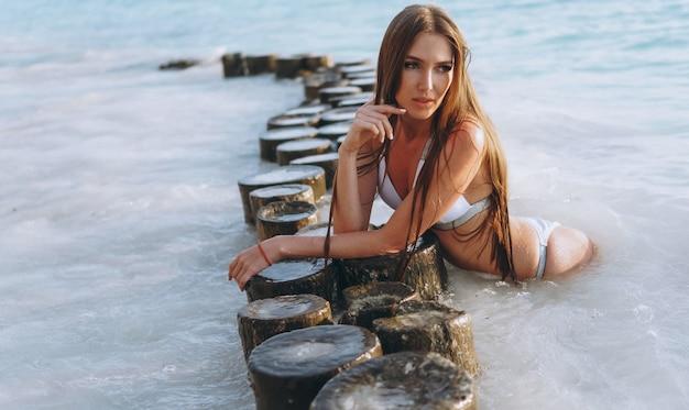 Sexy frau in der schwimmenabnutzung, die im ozean liegt