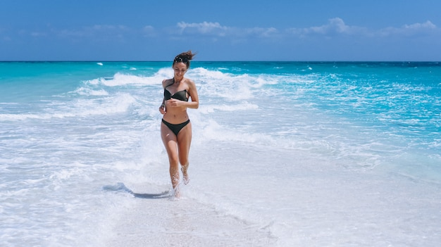 Sexy frau in der schwimmenabnutzung, die im ozean steht