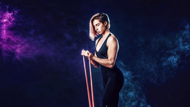 Sexy frau in der sportkleidung, die ein widerstandband in ihrem übungsprogramm verwendet. junge frau führt eignungsübungen auf schwarzer wand mit rauche durch. isolieren