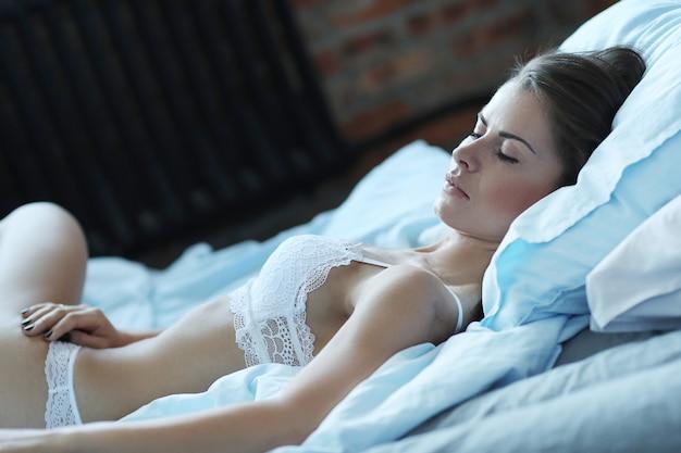 Sexy frau in dessous, die auf dem bett liegen