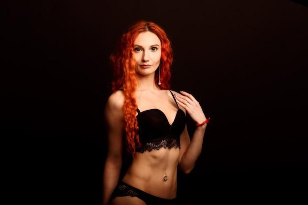 Sexy frau in dessous im schwarzen hintergrund, rote haare