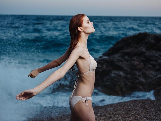 Sexy frau in einem badeanzug am strand nahe dem meer in der natur gestikuliert mit ihren händen.